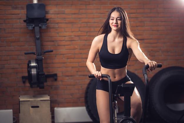 Frau, die ein übungsrad im fitnessstudio reitet. fit mädchen beim cardio-training auf dem fahrrad