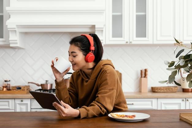 Frau, die ein video auf tablette betrachtet und kaffee trinkt