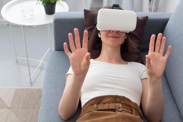 Frau, die ein videospiel spielt, während sie vr brillen benutzt