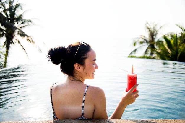 Frau, die ein wassermelonengetränk im pool genießt