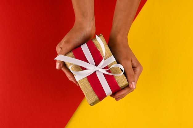 Frau, die ein weihnachts- oder geburtstagsgeschenk, hellen papierhintergrund gibt.