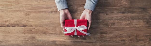 Frau, die ein weihnachts- oder geburtstagsgeschenk - netzfahne gibt