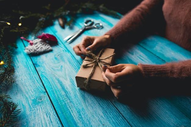 Frau, die ein weihnachtsgeschenk auf blauem hölzernem hintergrund verpackt