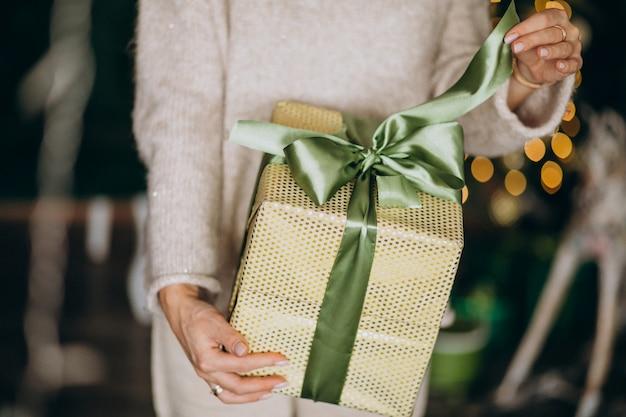 Frau, die ein weihnachtsgeschenk, kastenabschluß hochhält