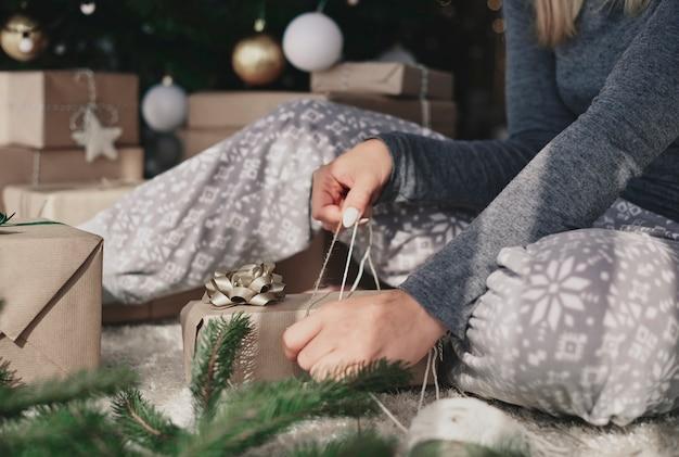 Frau, die ein weihnachtsgeschenk verpackt