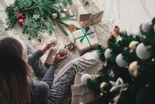 Frau, die ein weihnachtsgeschenk verziert