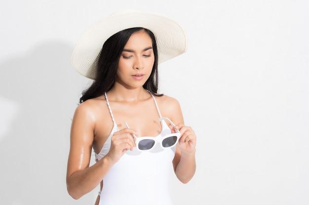 Frau, die ein weißes bikinikleid in einer stehenden position trägt und einen weißen weißen hut und eine sonnenbrille auf lokalisiertem weiß hält.