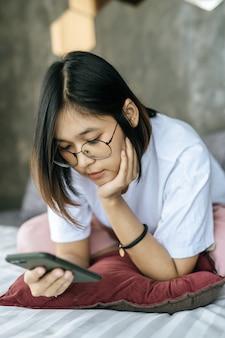 Frau, die ein weißes hemd trägt, das auf bett liegt und smartphone spielt.