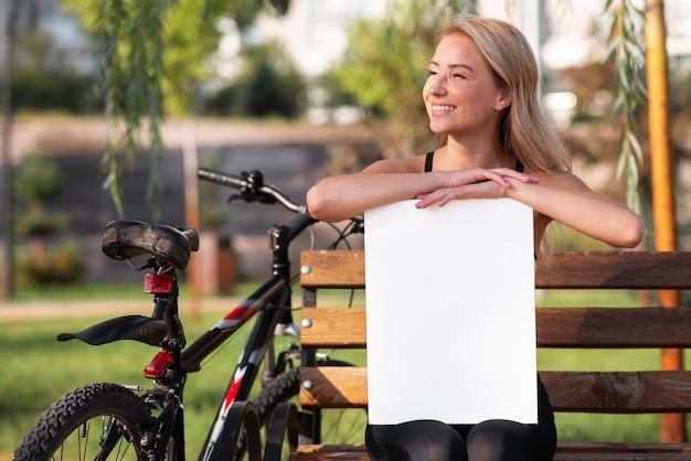 Frau, die ein weißes papier des kopienraums im park hält Premium Fotos