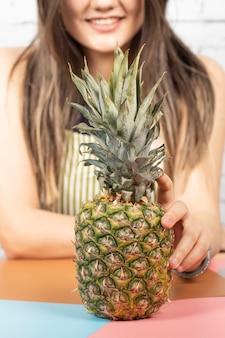 Frau, die eine ananas auf den tisch legt