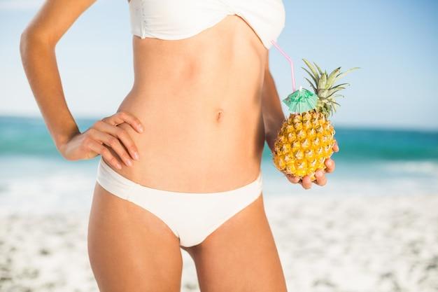 Frau, die eine ananas hält