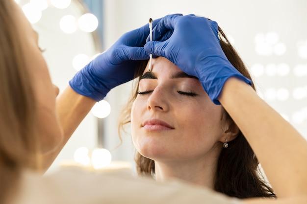 Frau, die eine augenbrauenbehandlung von einer kosmetikerin erhält