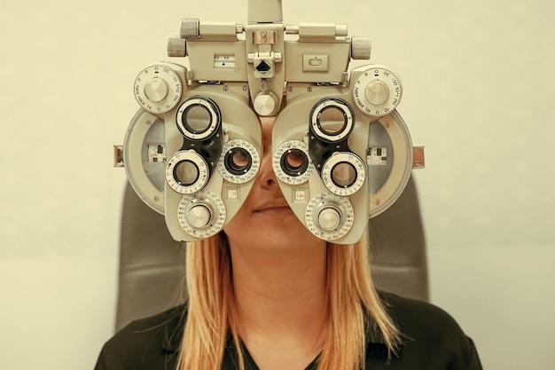 Frau, die eine augenuntersuchung durchführen lässt. weibliches optisches zentrum. messung der sehkraft einer frau in einer klinik
