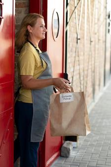 Frau, die eine bestellung bei einer abholung am straßenrand im freien aufgibt
