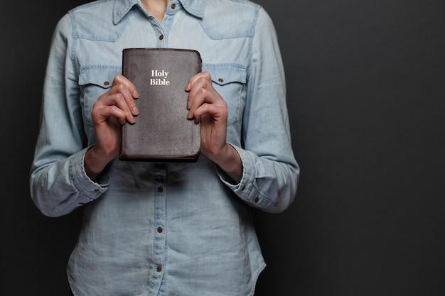 Frau, die eine bibel in den händen über dem grauen hintergrund hält. sie trägt freizeitkleidung