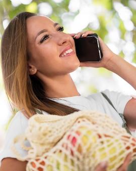 Frau, die eine biologisch abbaubare tasche hält, während sie am telefon spricht