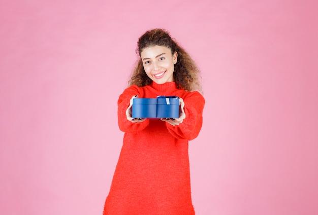 Frau, die eine blaue geschenkbox in herzform hält und sie ihrer freundin anbietet.
