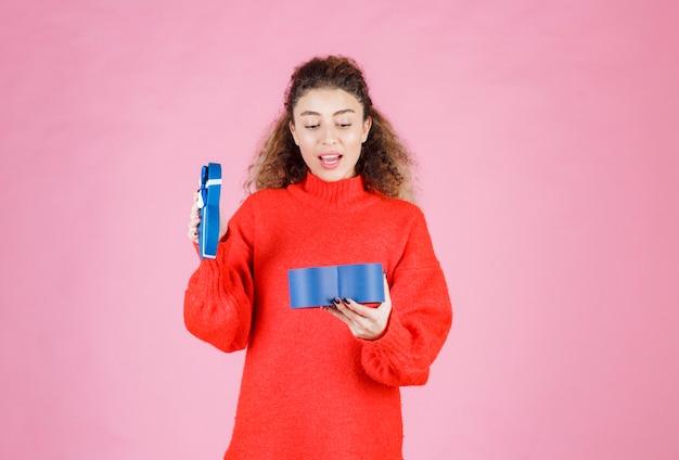 Frau, die eine blaue geschenkbox in herzform hält und sie öffnet.