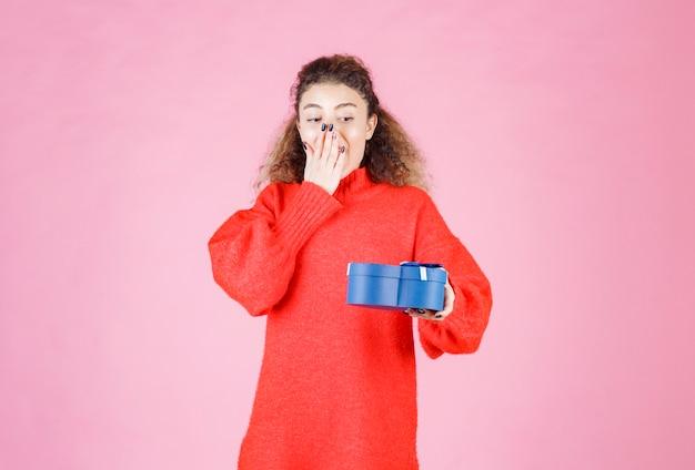 Frau, die eine blaue geschenkbox in herzform hält und überrascht aussieht.
