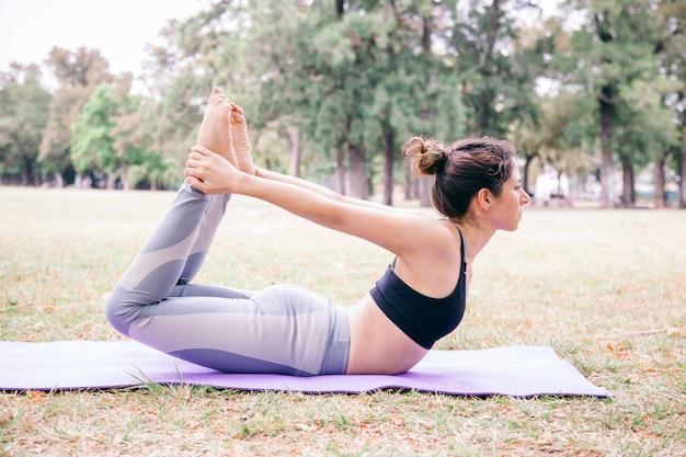 Frau, die eine bogenyoga-pose im freien tut. pilates gesunder lebensstil für menschen in yoga-übungen. training im freien und fit bleiben konzept. menschen, die wohlfühlmeditation im park machen.