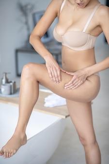 Frau, die eine cellulite auf ihren hüften prüft