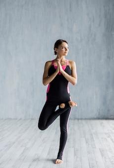 Frau, die eine einfache yogahaltung bei der stellung tut