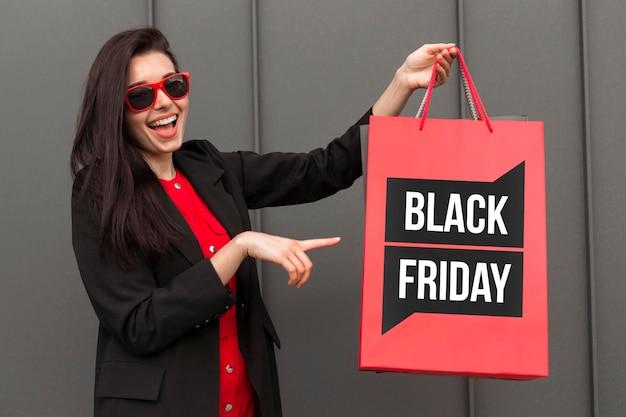 Frau, die eine einkaufstasche am schwarzen freitag hält