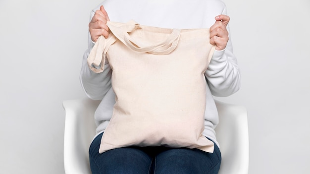 Frau, die eine einkaufstasche des kopierraumgewebes hält