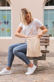 Frau, die eine einkaufstasche im freien trägt