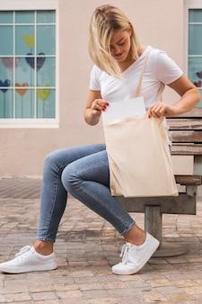 Frau, die eine einkaufstasche long shot trägt