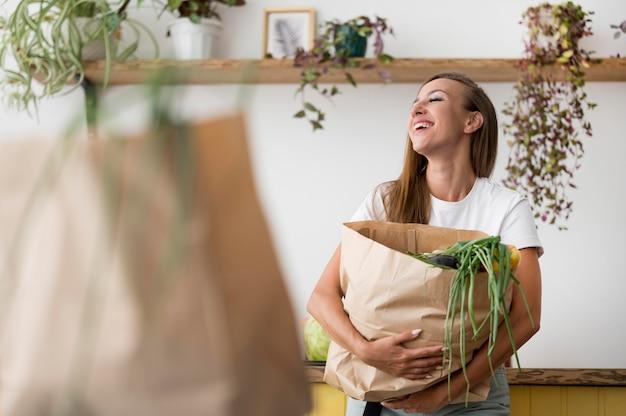 Frau, die eine einkaufstasche mit kopienraum hält