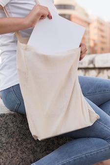 Frau, die eine einkaufstasche mit papieren trägt