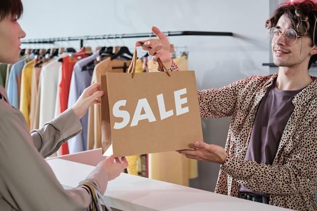 Frau, die eine einkaufstasche vom verkäufer nimmt, die sie während des verkaufs im laden kauft