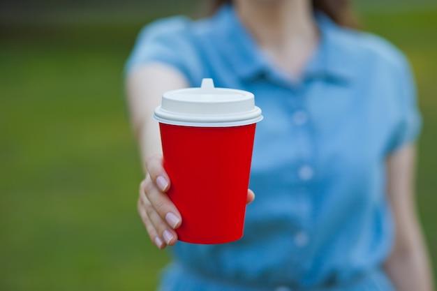 Frau, die eine einweg-pappbecher kaffee draußen wegnimmt.