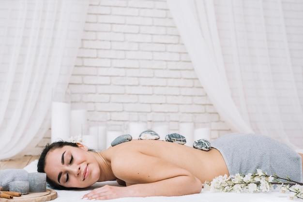 Frau, die eine entspannende steinmassage in einem badekurort empfängt