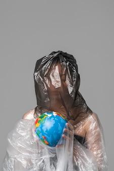 Frau, die eine erdkugel hält, während in plastik bedeckt wird