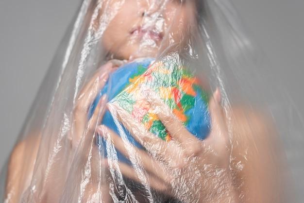 Frau, die eine erdkugel hält, während in plastiknahaufnahme bedeckt wird