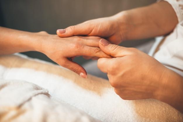 Frau, die eine fingermassage zur hand hat, während sie im bett im spa-salon liegt