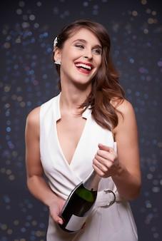 Frau, die eine flasche champagner hält