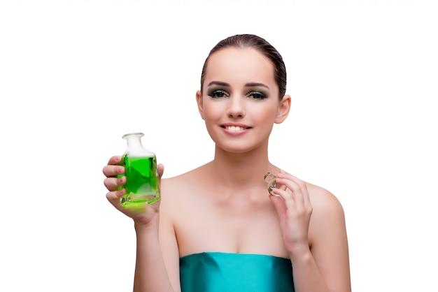 Frau, die eine flasche grünes parfüm hält