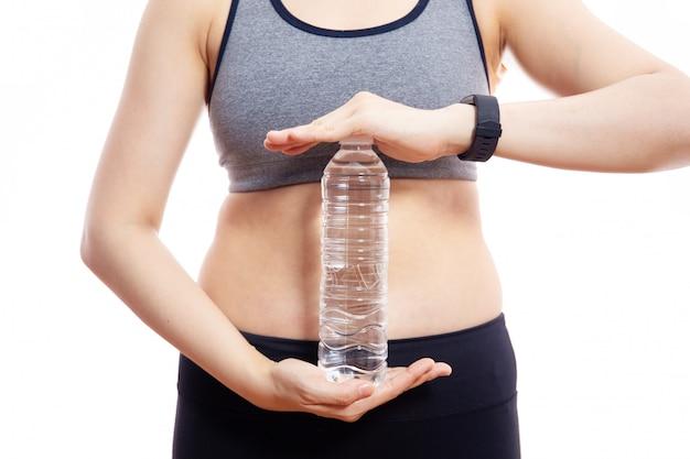 Frau, die eine flasche trinkwasser hält.