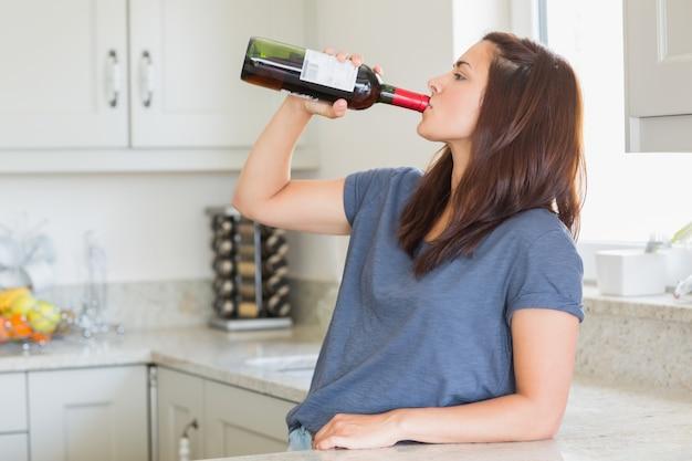 Frau, die eine flasche wein alleine trinkt