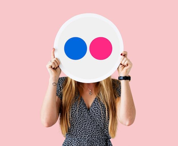 Frau, die eine flickr-ikone hält