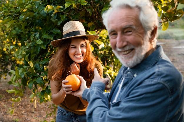 Frau, die eine frische orange mit ihrem vater hält