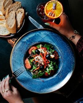Frau, die eine gabel setzt, um gemischten saisongemüsesalat innerhalb der blauen platte zu essen.