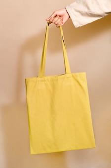 Frau, die eine gelbe einkaufstasche in der hand hält