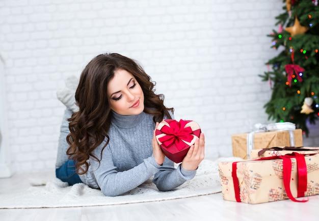 Frau, die eine geschenkbox hält, die wie ein herz geformt wird