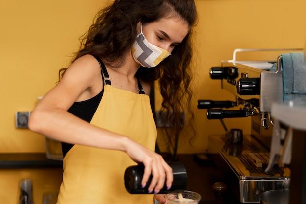 Frau, die eine gesichtsmaske beim kaffeekochen trägt