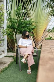 Frau, die eine gesichtsmaske sitzt, die auf einem stuhl neben einem schwimmbad im garten sitzt.