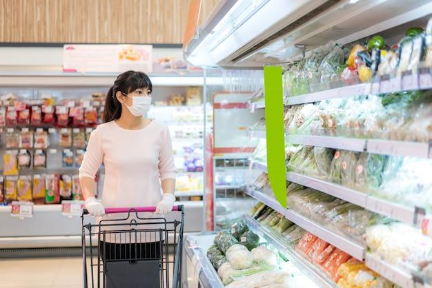 Frau, die eine gesichtsmaske und chirurgische handschuhe in einem supermarkt trägt